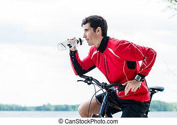 Hombre deportivo en bicicleta de montaña bebiendo agua en reposo