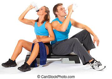 Hombre deportivo y mujer bebiendo agua después del entrenamiento