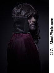 Hombre diablo con pelo largo y abrigo negro