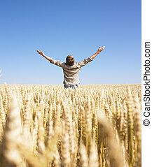 Hombre en campo de trigo con brazos extendidos