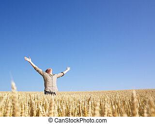 Hombre en el campo de trigo con brazos extendidos