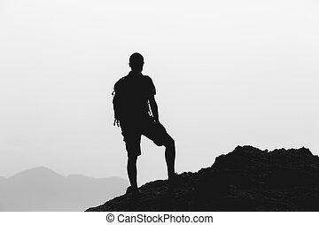 Hombre escalando paisajes de inspiración, silueta de viaje