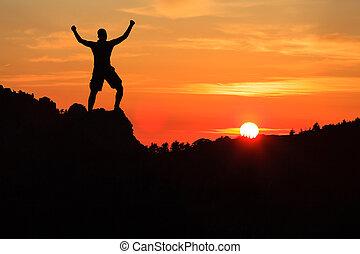 Hombre escalando silueta en montañas del atardecer
