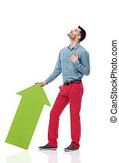 Hombre feliz con flecha verde mirando hacia arriba