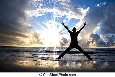 Hombre feliz saltando en la playa con hermoso amanecer