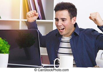 Hombre joven celebrando con entusiasmo por delante de la computadora portátil