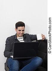 Hombre joven en la casa del sofá con la computadora portátil