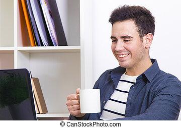 Hombre joven tomando café en el escritorio con la computadora portátil