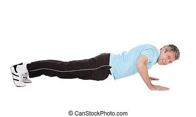 Hombre maduro activo haciendo flexiones