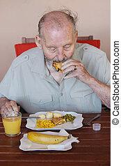 Hombre mayor comiendo comida saludable en casa