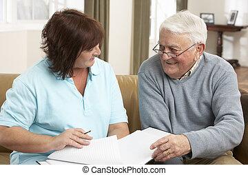Hombre mayor en discusión con visitante de la salud en casa