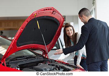 Hombre mostrando el motor del auto