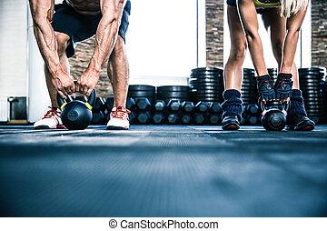 Hombre musculoso y mujer en forma de entrenamiento con una bola de agua