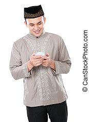 Hombre musulmán sosteniendo teléfono móvil