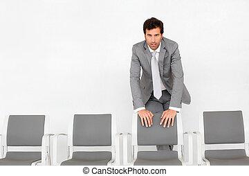 Hombre parado junto a sillas en la sala de espera