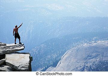 Hombre parado sobre un precipicio con el brazo levantado