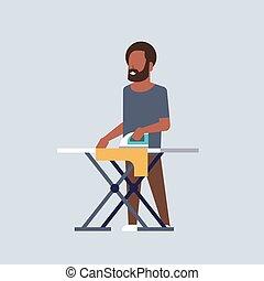 Hombre planchando ropa afro-americano sosteniendo hierro haciendo tareas domésticas concepto de dibujos animados masculinos de largo y ancho fondo gris