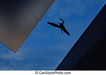 Hombre saltando sobre el techo del edificio contra fondo del cielo azul
