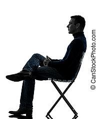 Hombre sentado de lado, silueta de largo