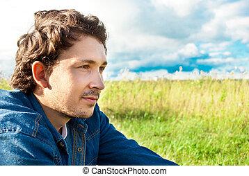 Hombre sentado en un campo