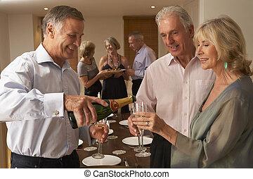 Hombre sirviendo champaña a sus invitados en una cena