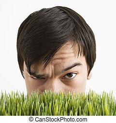 Hombre sospechoso tras la hierba.