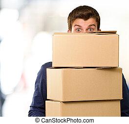 Hombre sosteniendo cajas de cartón