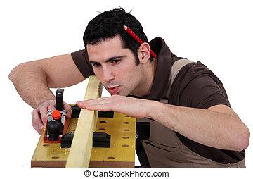 Hombre suavizando tablas de madera con avión