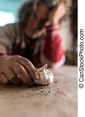 Hombre triste mirando la bombilla de ajo sosteniéndola con las manos sucias