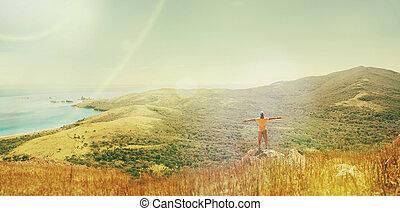Hombre viajero parado en la cima de la montaña cerca del mar