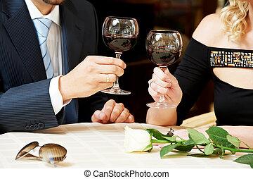 Hombre y chica toman vino en el café en una cita