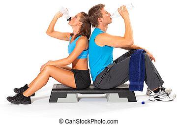 Hombre y mujer bebiendo agua después de hacer ejercicio