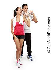 Hombre y mujer bebiendo agua después del ejercicio