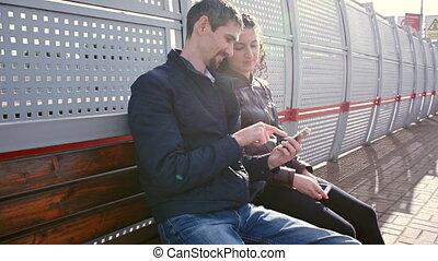 Hombre y mujer están esperando el tren en la plataforma