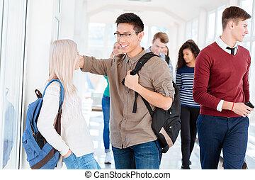 Hombre y mujer hablando en el pasillo de la universidad