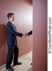 Hombres de negocios estrechando la mano en el corredor de la oficina