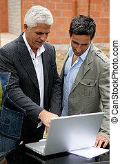 Hombres en un edificio con una laptop