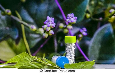 Homeopathic Concept - Botellas de píldoras de azúcar homeopáticas en hojas verdes con un fondo de flores púrpura borroso