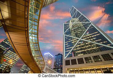 Hong Kong por la noche. Pasaje peatonal sobre el nivel de la calle y alrededor de majestuosos rascacielos del centro. Una vista amplia.