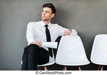 Hora de esperar. Un joven pensativo sosteniendo papel sentado en una silla contra el fondo gris