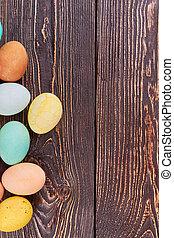 Huevos de color en madera marrón.