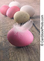 Huevos de Pascua con plumas en la mesa de madera