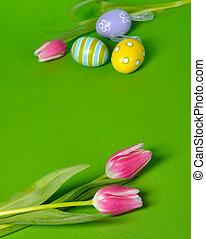 Huevos de Pascua y tulipanes en verde fondo con espacio de copia
