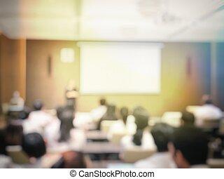 Imágenes borrosas de la educación y gente de negocios sentados en la sala de conferencias para seminarios de profesión y el orador está presentando con proyector de pantalla y compartir ideas con la actividad del contenido.