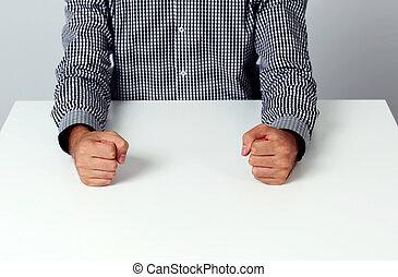 Imágenes de dos puños en una mesa blanca