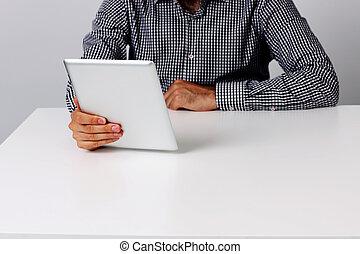 Imágenes de un hombre sentado en la mesa y sosteniendo una computadora de tablet