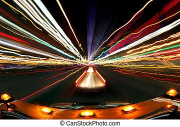 Imagen borrosa intencional de conducir de noche con las luces de la ciudad y