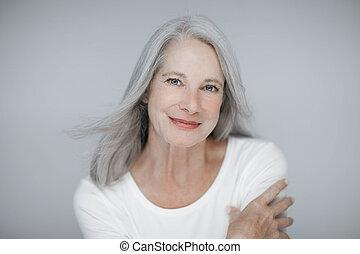 Impresionante hermosa y segura de sí misma la mejor mujer de edad con el pelo gris sonriendo a la cámara