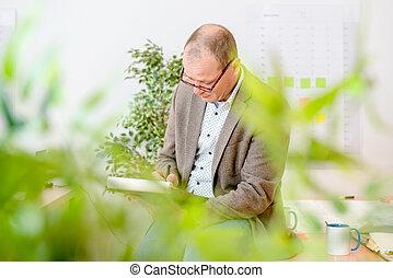 Ingeniero haciendo planes en Notepad en el lugar de trabajo
