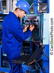Ingeniero industrial reparando máquina computarizada